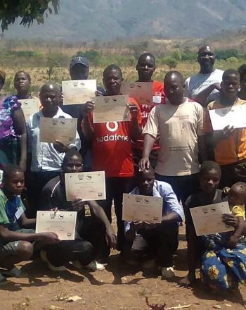 Group holding certificates, hills in background.