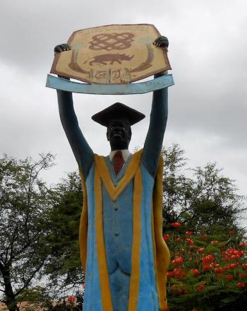 Large statue of graduate holding up sign.