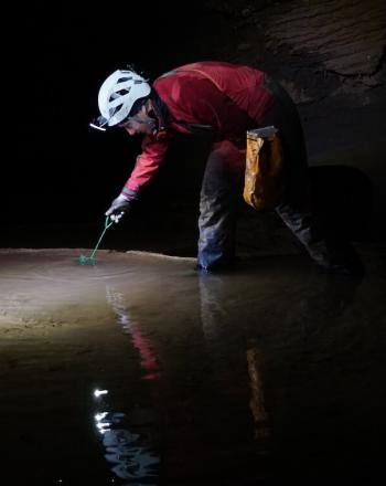 Man standing in cave, taking sample from water.