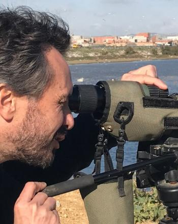 Close-up of man looking through a monocular, water behind him and buildings in background.