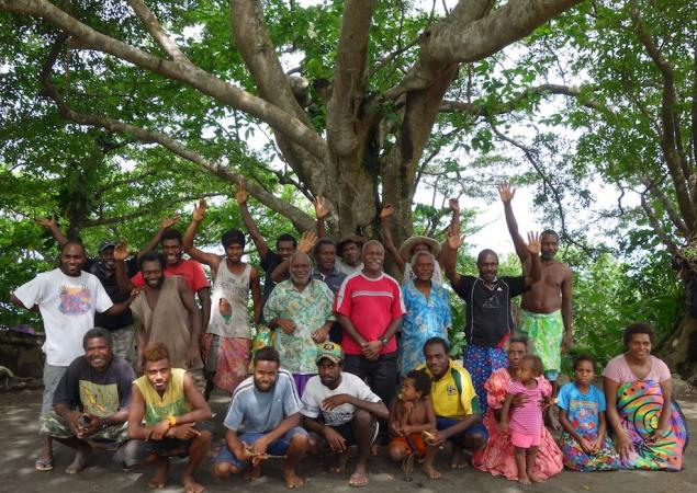 Several men, women and children gather and wave for a group photo in front of a large tree in Tafea Province, Vanuatu.
