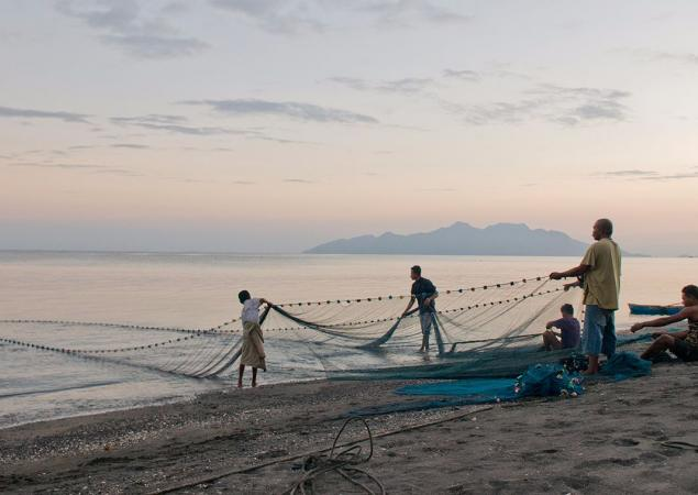 Small group of men stand on a beach, pulling a large net from the water, Flores Island, Indonesia.