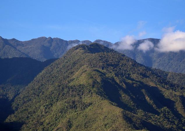 Heavily forested mountain tops with clouds floating above.