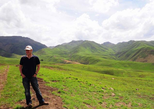 A man stands in a green grassland with mountains in the background.
