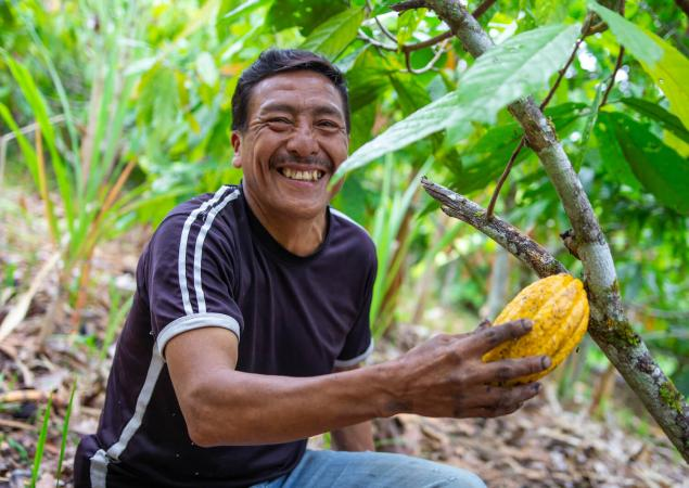 Man smiles at camera, holds up large, yellow seed.