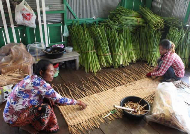 Two women sit at different ends of a mat they are weaving out of plants.