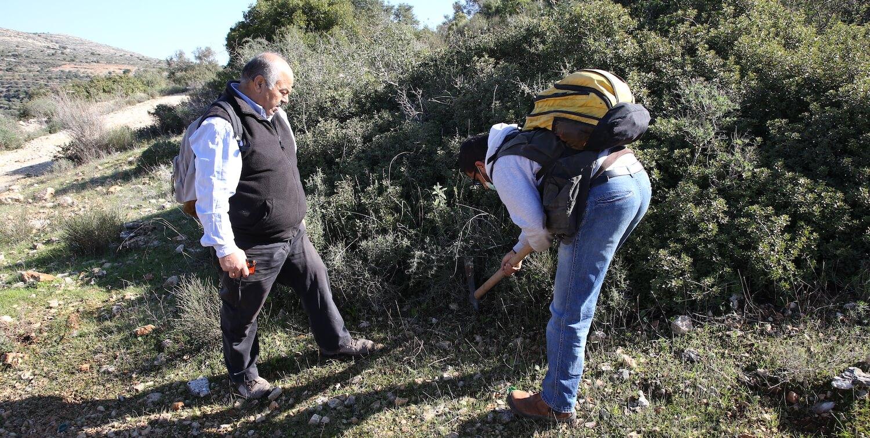 Two men surveying ground next to bush.