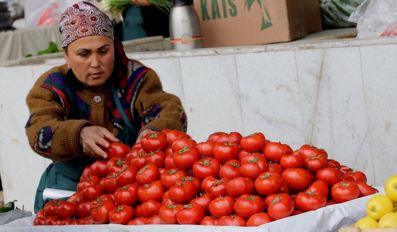 Woman with a mound of tomatoes for sale.
