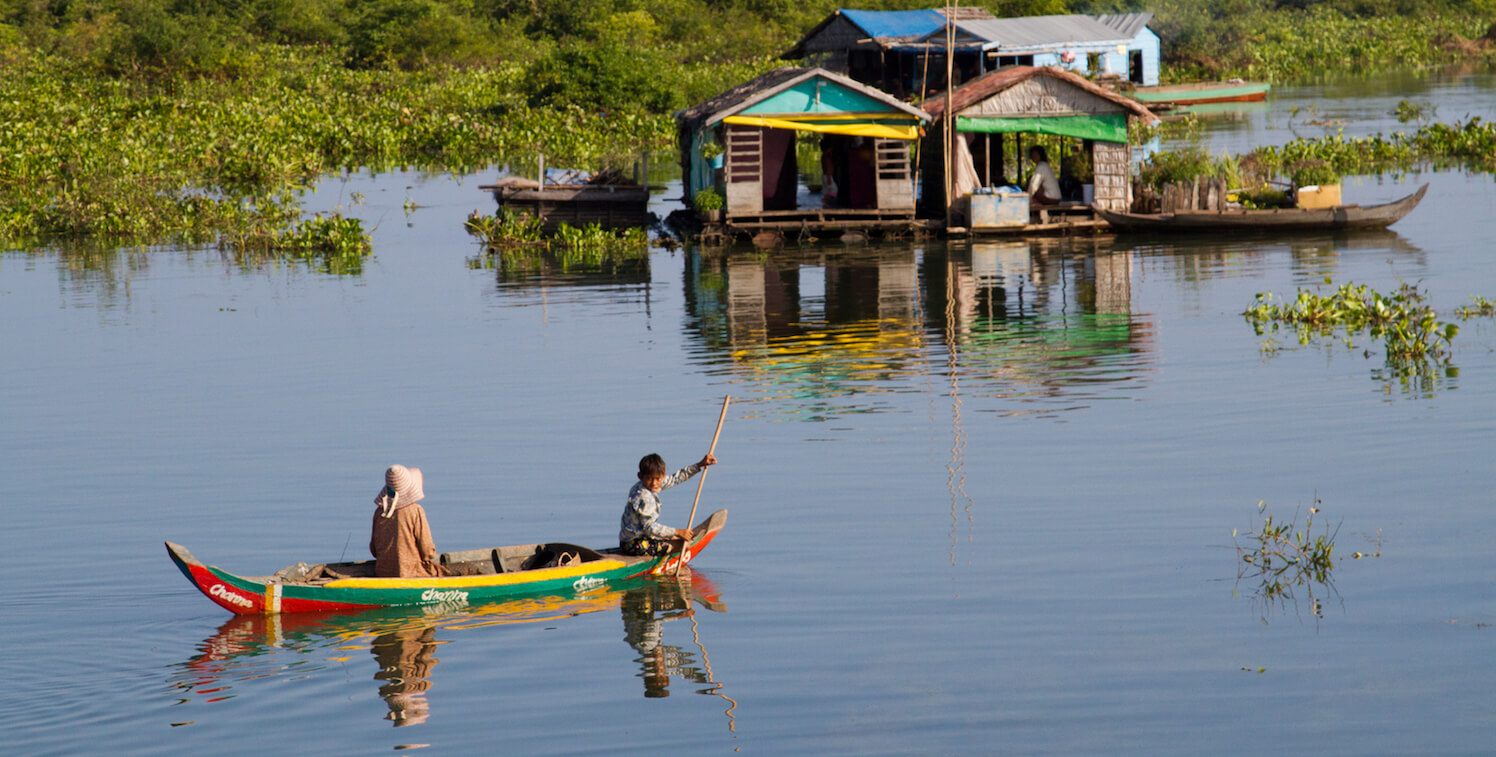 Two people in canoe near several floating buildings.