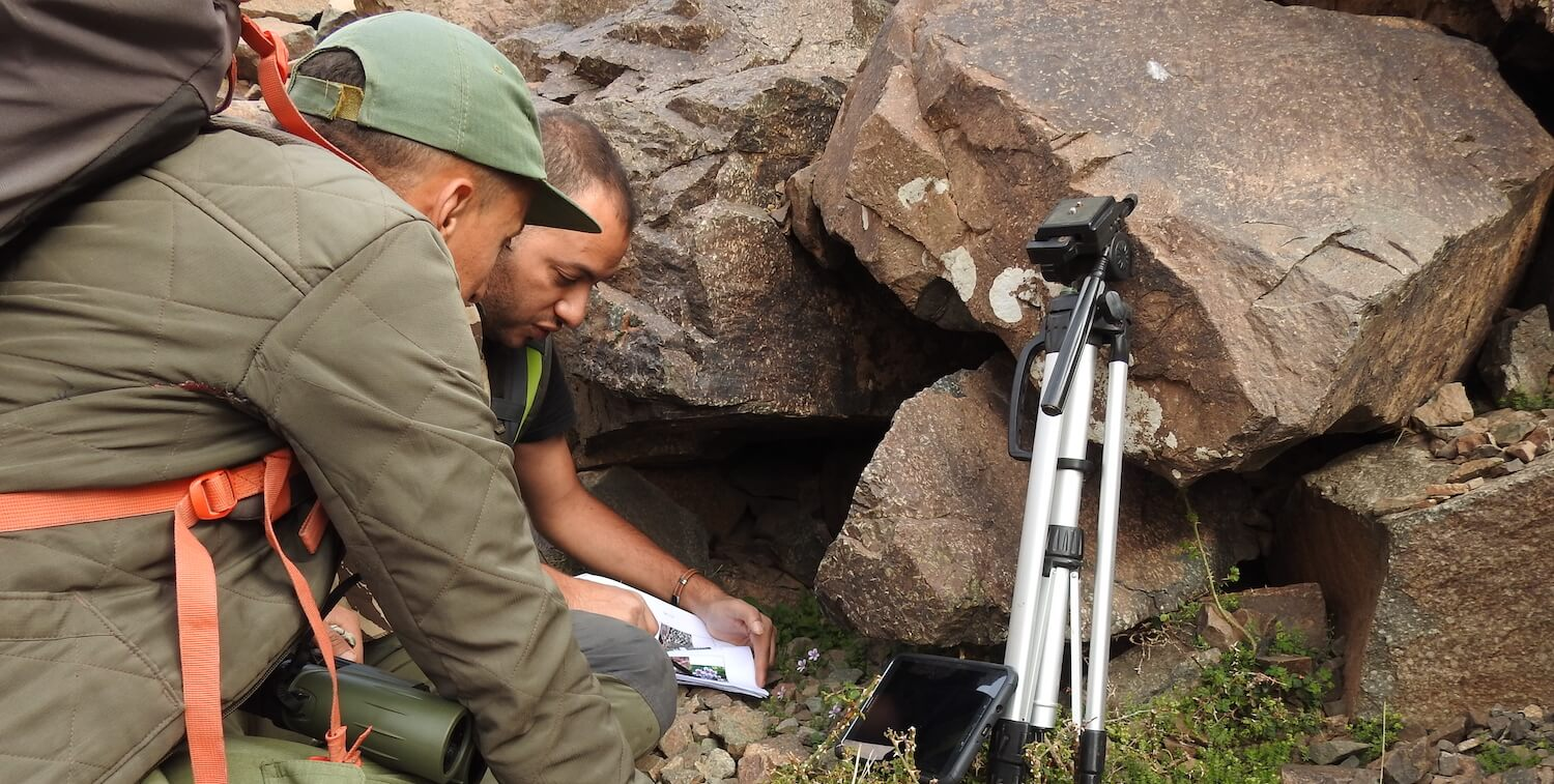 Two men crouching down near boulders, examining papers.