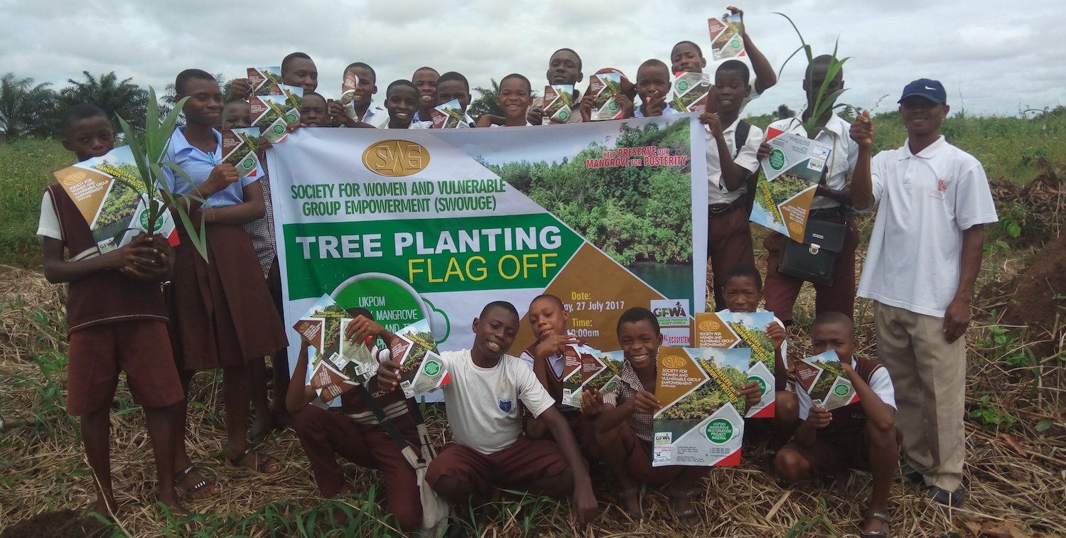 Group of boys stand around tree planting sign, outside.