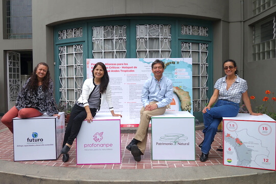 Three women and 1 man, each sitting on a cardboard box, part of a display outside a building.