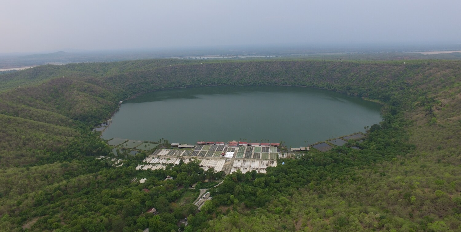 Aeriel view of volcanic lake with large facilities on one shore.