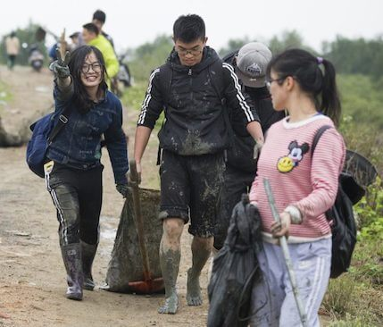 Three young people, muddy, carrying trash bags. One smiles at the camera and holds up the peace sign.