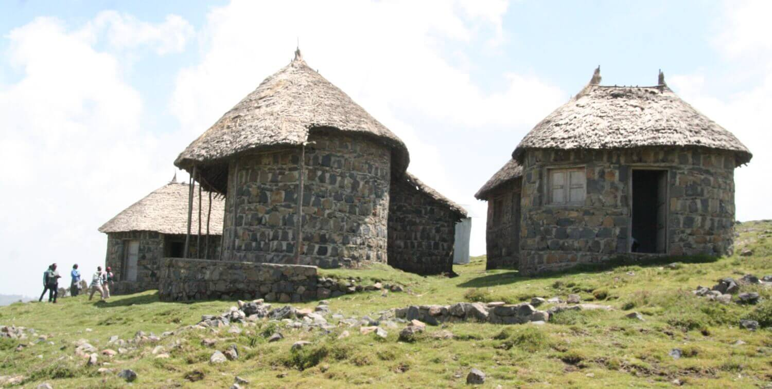Round buildings with thatched roofs.