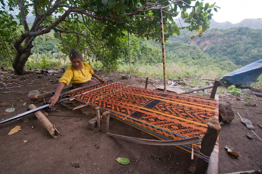 Woman works outside at a large loom.