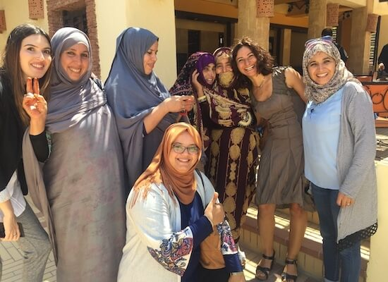 Group of women smiling, many wear headscarves.